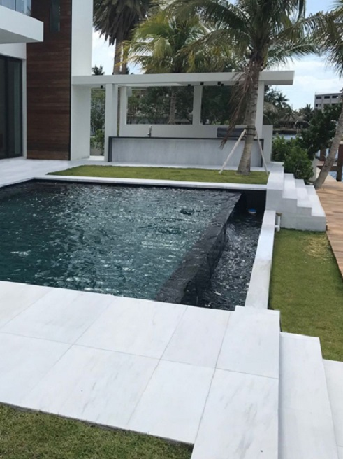 poolside with ice white sandblasted marble and palm trees