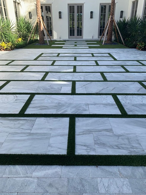 house entrance with ice white marble pavers and grass