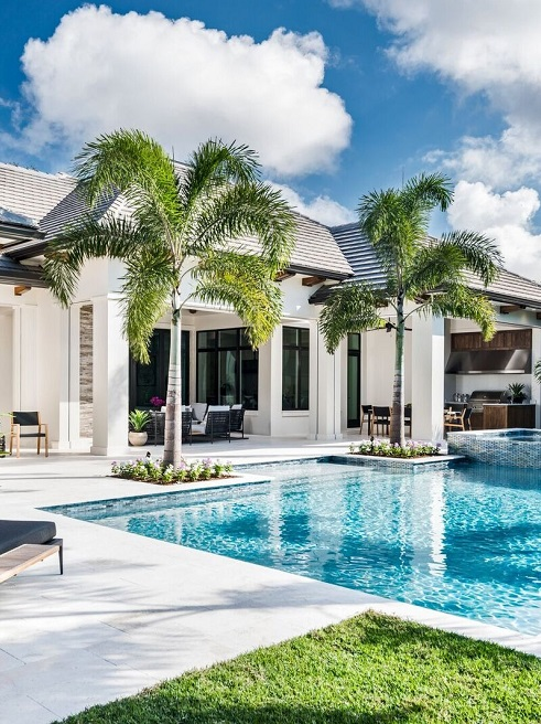 poolside of a villa with shell beige limestone and couple palm trees