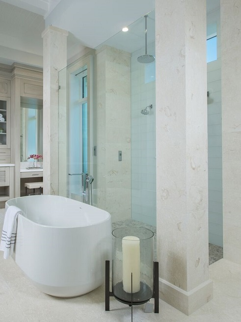 bathroom design with white bathtub and shell beige limestone tiles on wall
